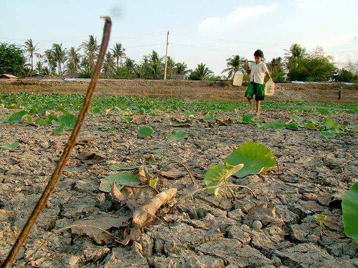A child  walks across a dried pond as he carries water in southern Yangon in 2010.