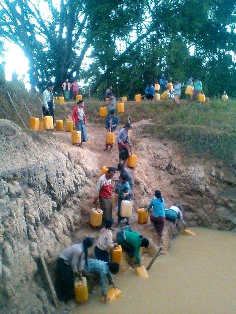 Villagers fetch water from a lake at a village in Heho Township.