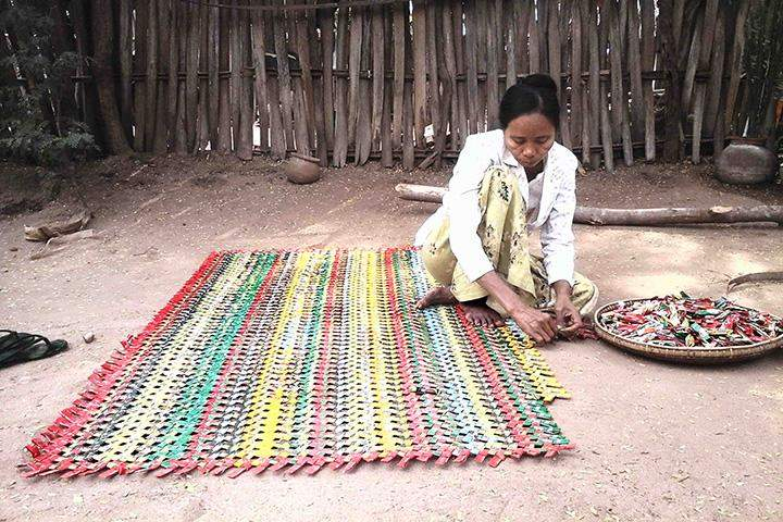 A woman making the mat with the use of sachets of instant coffee mix.