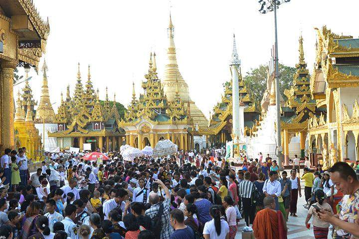 Devotees throng to a procession of Buddhist monks to donate dry ration.