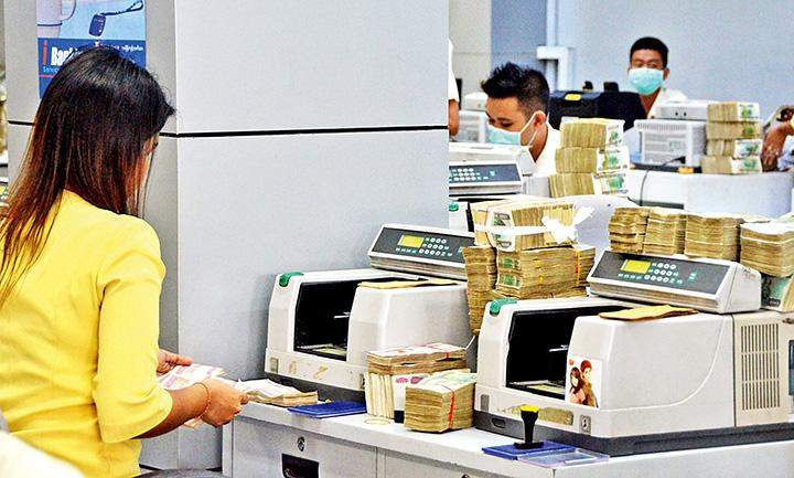 A member of staff of a local seen bank counting cash.