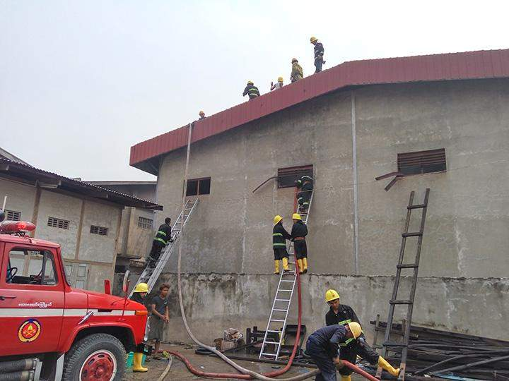 Firemen extinguish the fire at the warehouse in Mandalay.