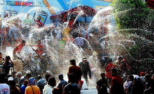 People having fun under splash of water during water festival.