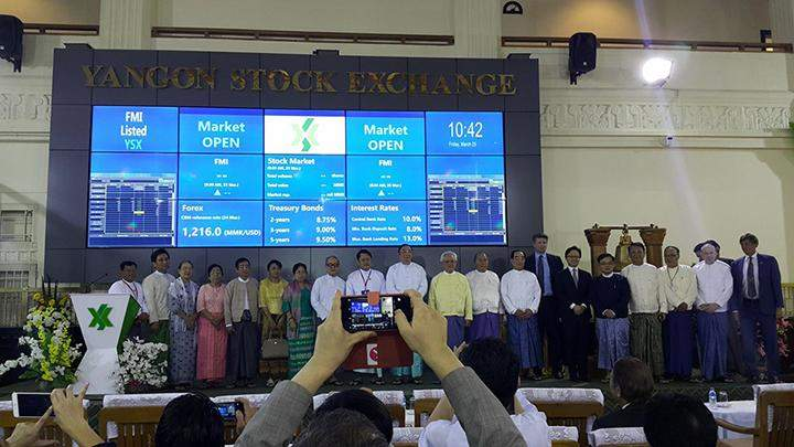 Government officials and business people pose for documentary photos at the opening of the Yangon Stock Exchange in Yangon.
