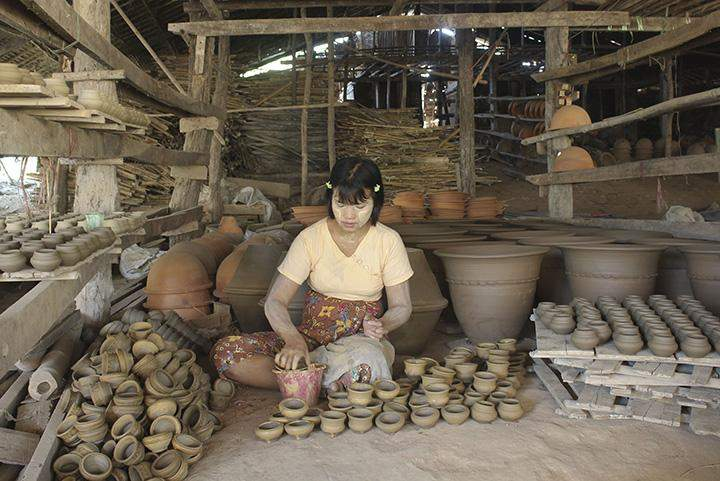 A woman makes small clay toy pots in Twantay.