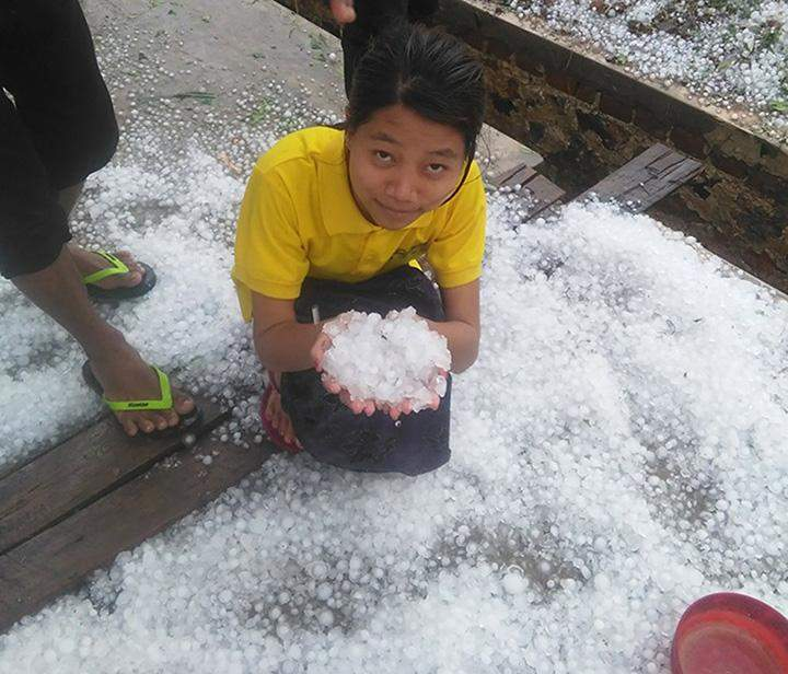 A girl collects hailstones in Sagaing.