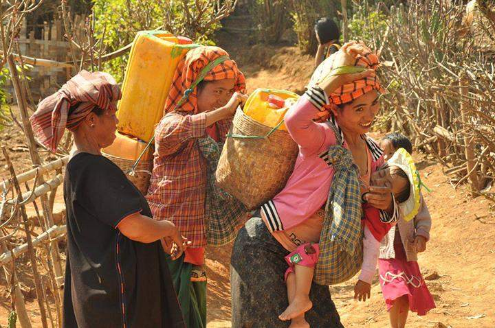 Ethnic women seen carrying water supplied by KBZ Foundation.