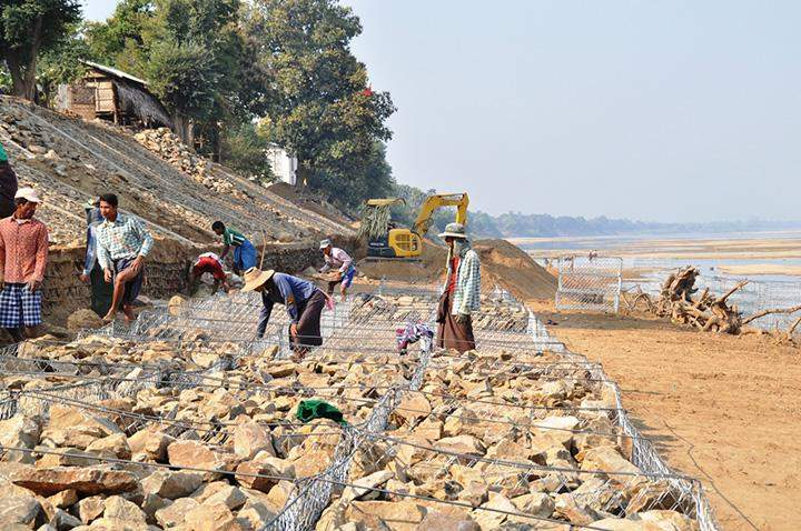 Workers lay stones at the bank of Ayeyawady River in Mandalay to prevent erosion.