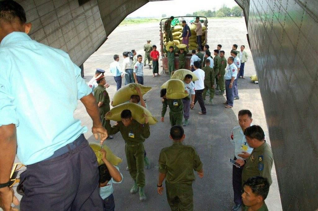 Tatmadawmen loading sacks of rice onto the aircraft.