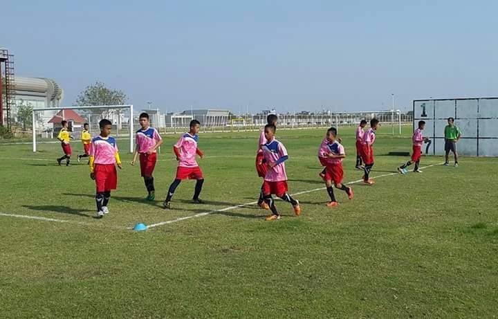 School children receive soccer skills in summer in Yangon.