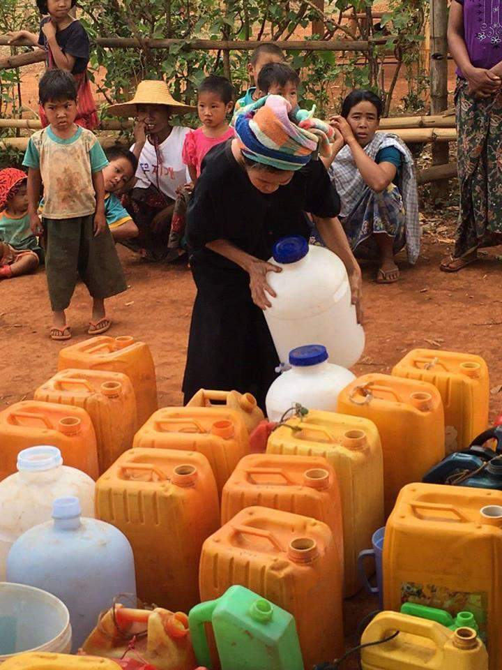 An ethnic woman fills plastic containers with water supplied by KBZ Brighter Future Myanmar foundation.
