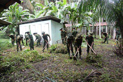 Soldiers clean up bushes and branches in a Maygon school.