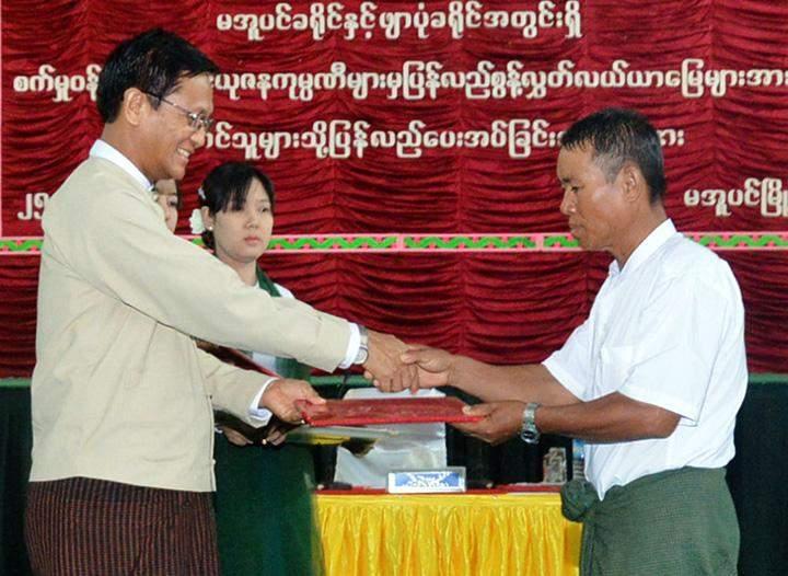 Vice President U Henry Van Thio presents document to a farmer at the ceremony to return farmland to farmers in Ayayawady Region.