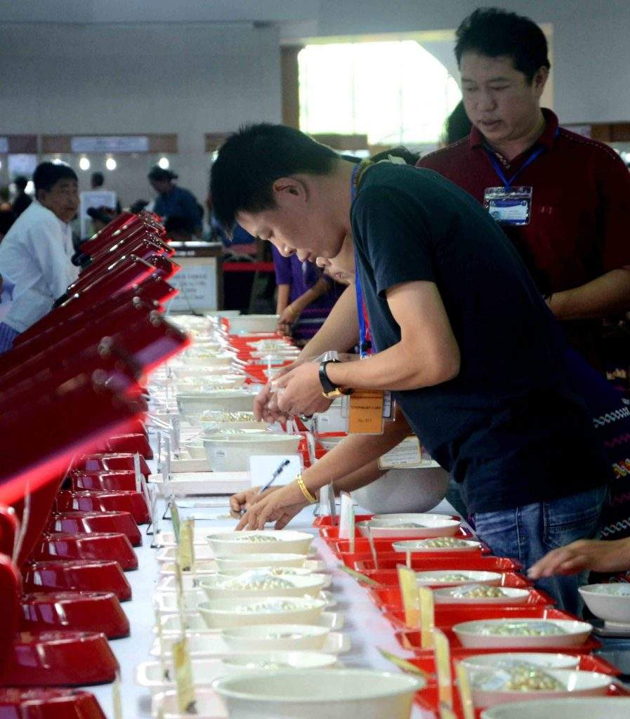 Traders check pearl at the gems emporium in Nay Pyi Taw.  Photo: Aye Than