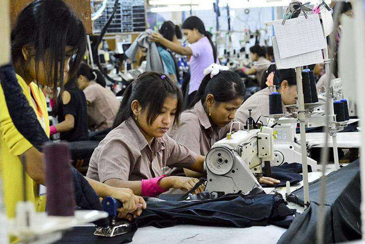 Employees work at a production line of a garment factory in Hlinethaya Industrial Zone.