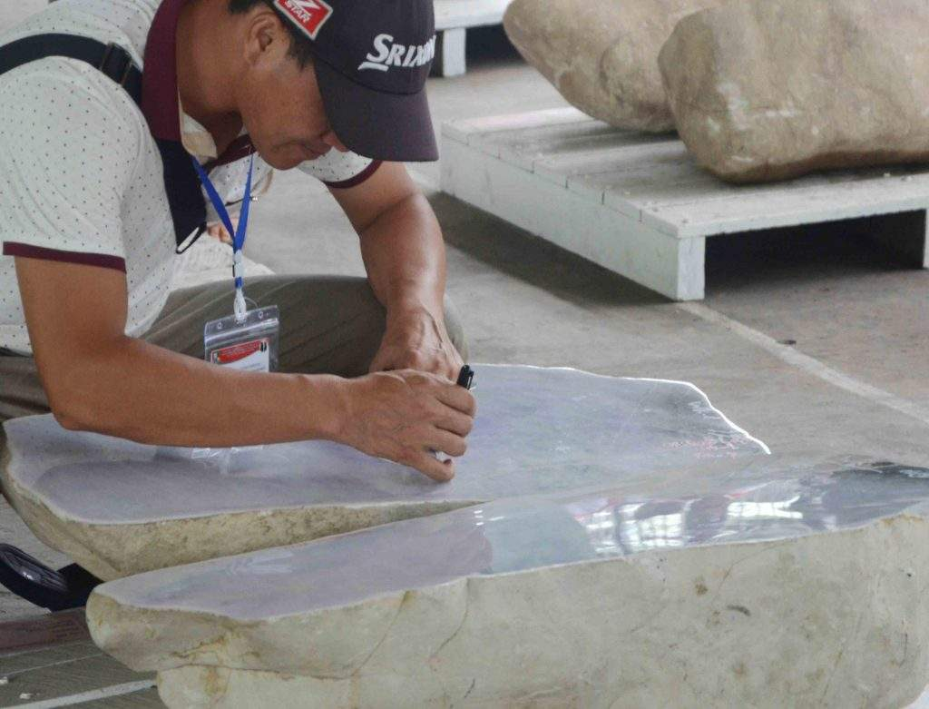 A merchant checks a jade stone during the 53rd Myanmar Gems Emporium in Nay Pyi Taw. Photo: MNA