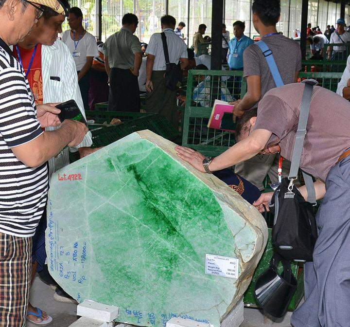 Traders check a jade stone at the 53rd Myanmar Gems Emporium in Nay Pyi Taw.