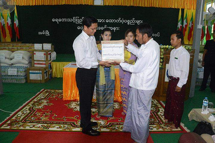 Vice President U Henry Van Thio presents cash assistance to local authority.