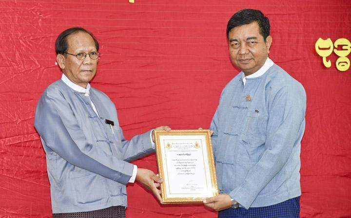 U Nyo Myint (R) accepts a certificate of honour presented by U Tin Zaw.
