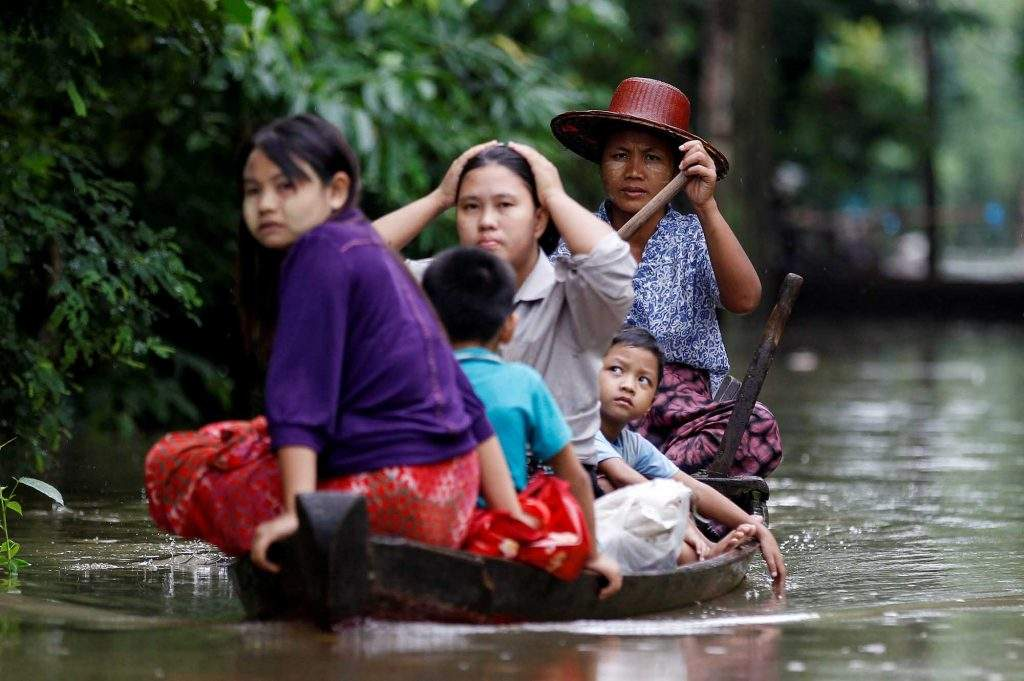 A family rows their boat through a flooded road in Kyaung Kone in Ayeyarwady Region, August 12, 2016. Photo: Reuters