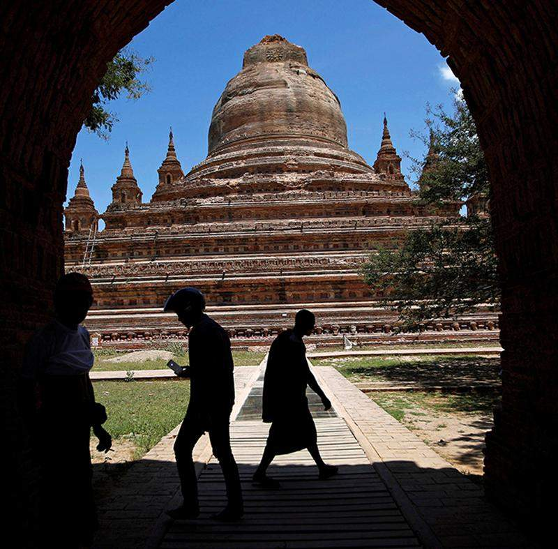 People walk as the top of a collapsed pagoda is seen in the background after an earthquake in Bagan on 25 August 2016.