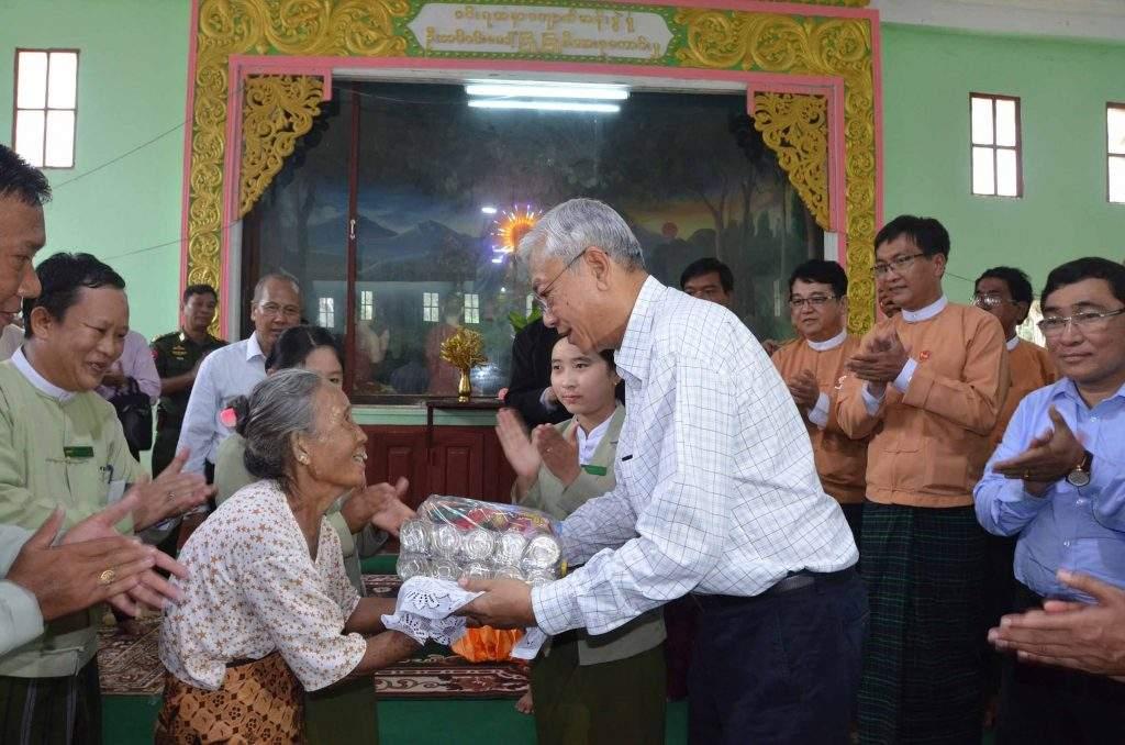 President U Htin Kyaw presents aid to an elder woman in Minbu. Photo: MNA