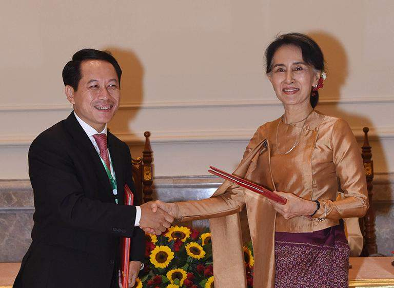 Union Foreign Affairs Minister Daw Aung San Suu Kyi shakes hands with Laotian counterpart Mr Saleumxay Kommasith after exchanging notes of agreement for management of the friendship bridge.