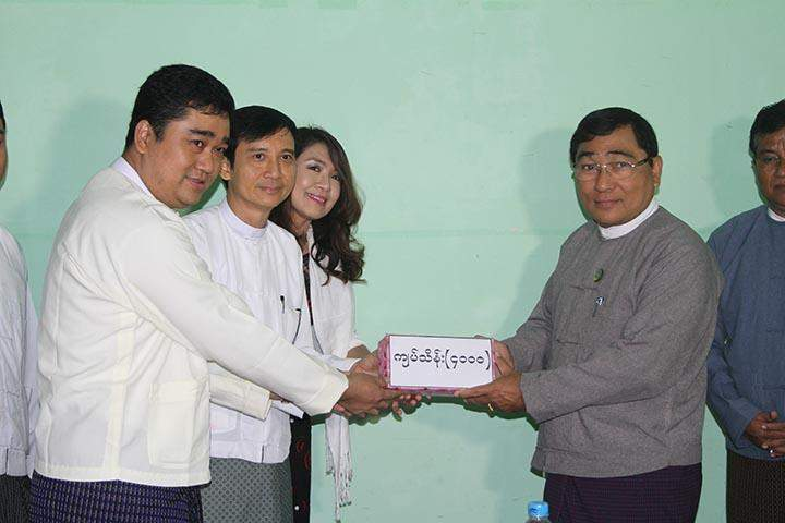 U Than Win Swe of IGE Group of Companies presents K400 million to Union Minister Dr Win Myat Aye.