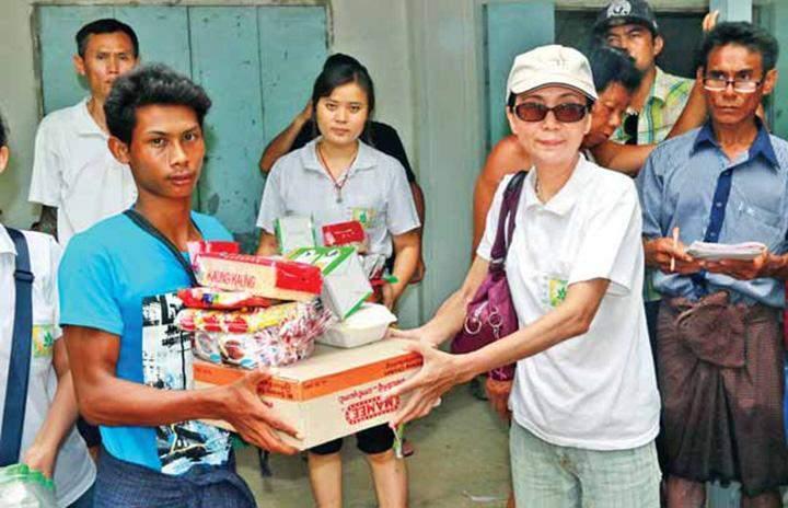 A member of Myat Cetana Mon social assistance  association presents food to a  flood victim.