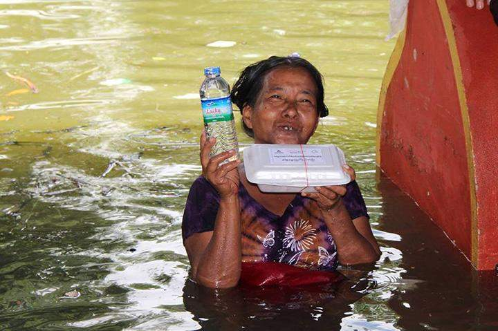 An old woman holding a meal box and a purified drinking water bottle donated by KBZ's Brighter Future Myanmar Foundation.