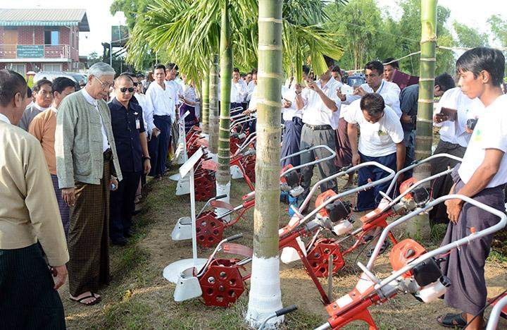 President U Htin Kyaw inspects farming implements during his visit to the 200-acre integrated farm in Toungoo.