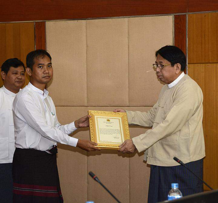 Union Minister for Information Dr Pe Myint presents the President's Certificate of Honour to Chief Reporter U Swe Win of the Myanmar Now News Agency.