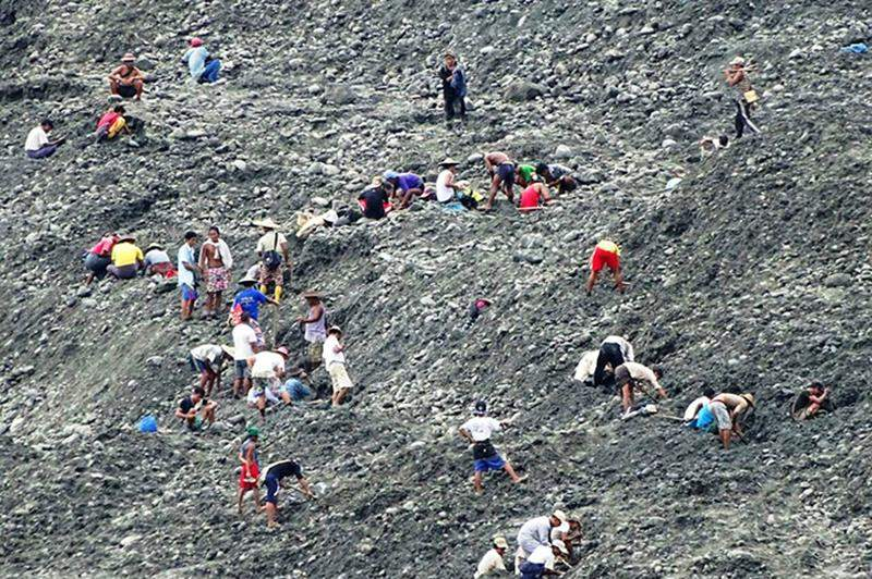 Seekers search jade at the mountain of soil dumped by mining companies in Kani township.