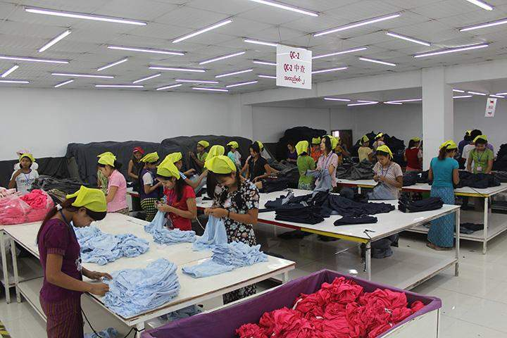 Workers are seen at the production line of a garment factory in Yangon.