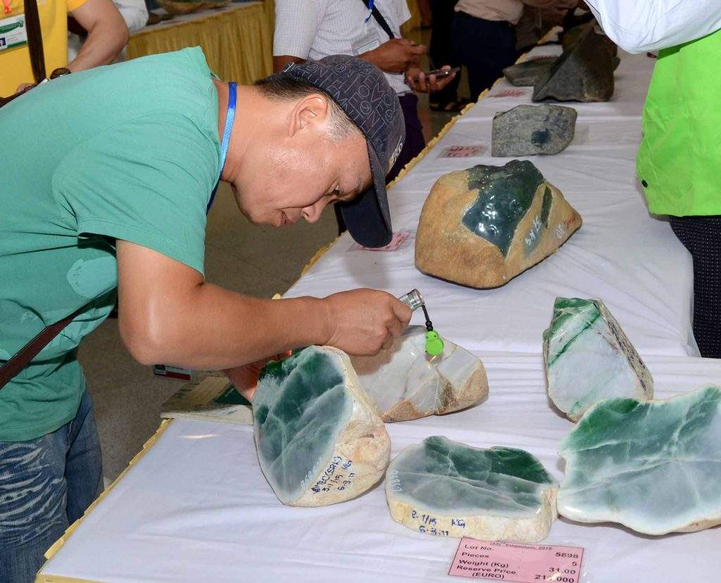 A foreign trader checks jade stones at the mid-year emporium in Nay Pyi Taw last year. Photo: MNA