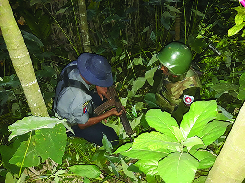 Service personnel check the weapon hidden by violent attackers in Maungtaw Township.