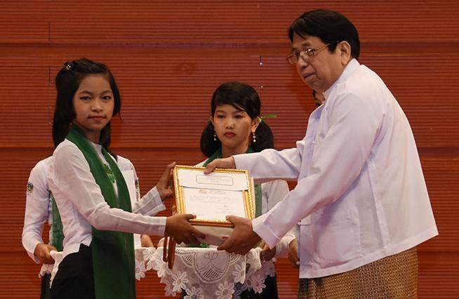 Union Minister Dr Pe Myint presents a prize to the winner of the story telling contest at the Children's Literature Festival.