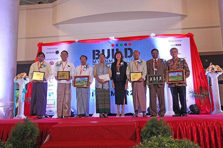 Attendees of a Build Myanmar conference posing for a group photograph.