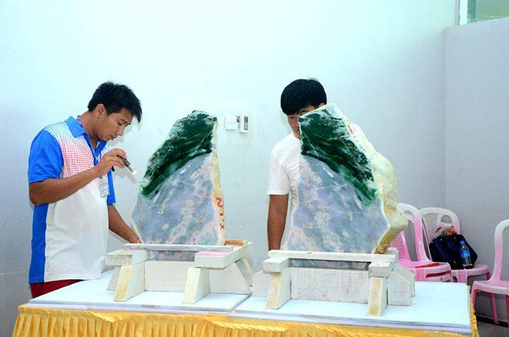 Merchants appraise a jade stone at the 53rd Myanmar Gems Emporium in Nay Pyi Taw.