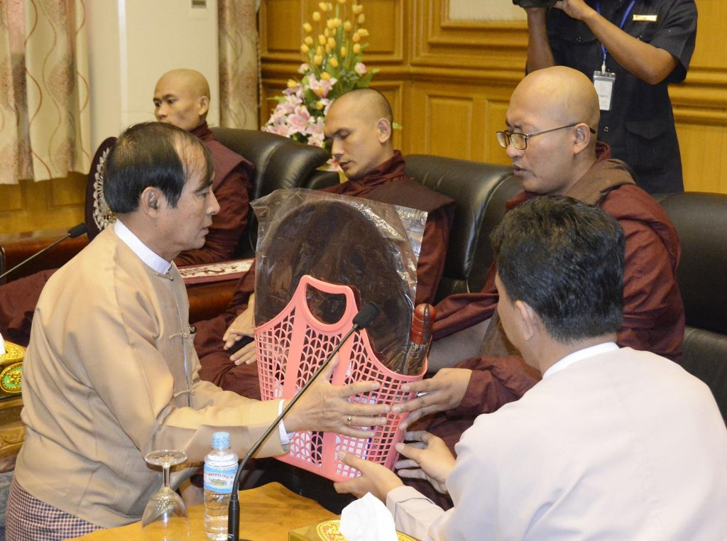 Pyithu Hluttaw Speaker U Win Myint donates offertories to a Member of the Sangha at the Paritta reciting ceremony held at Pyithu Hluttaw office in Nay Pyi Taw. Photo: MNA