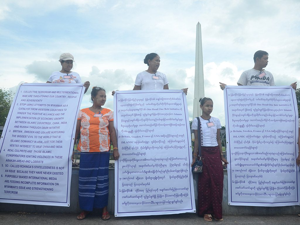 Protestors hold placards denouncing some western countries' interference in and international media's bias coverage on Rakhine State issue during the demonstration organized by Myanmar Political Watchers in downtown Yangon, on 2nd October, 2017. Photo: Phoe Khwar