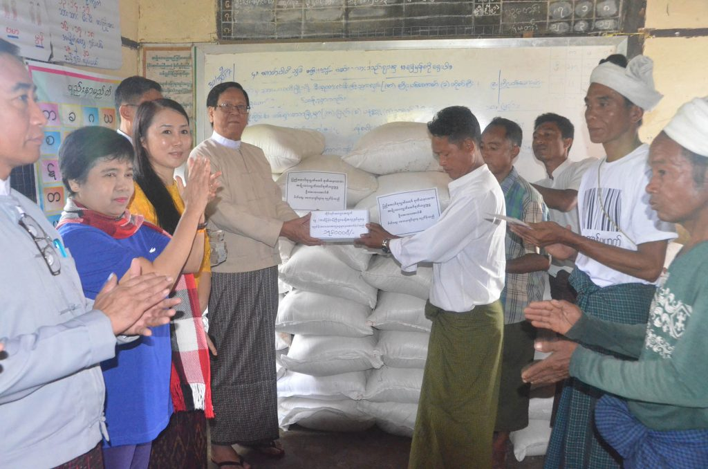 Deputy Speaker U Aye Thar Aung provides rice and cash assistance to displaced people in a village in northern Rakhine. Photo: MNA