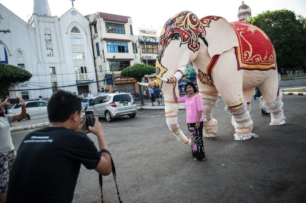 A visitor takes a picture of a paper mache elephant at the Mahabandoola Park, Yangon. Photo: Supplied