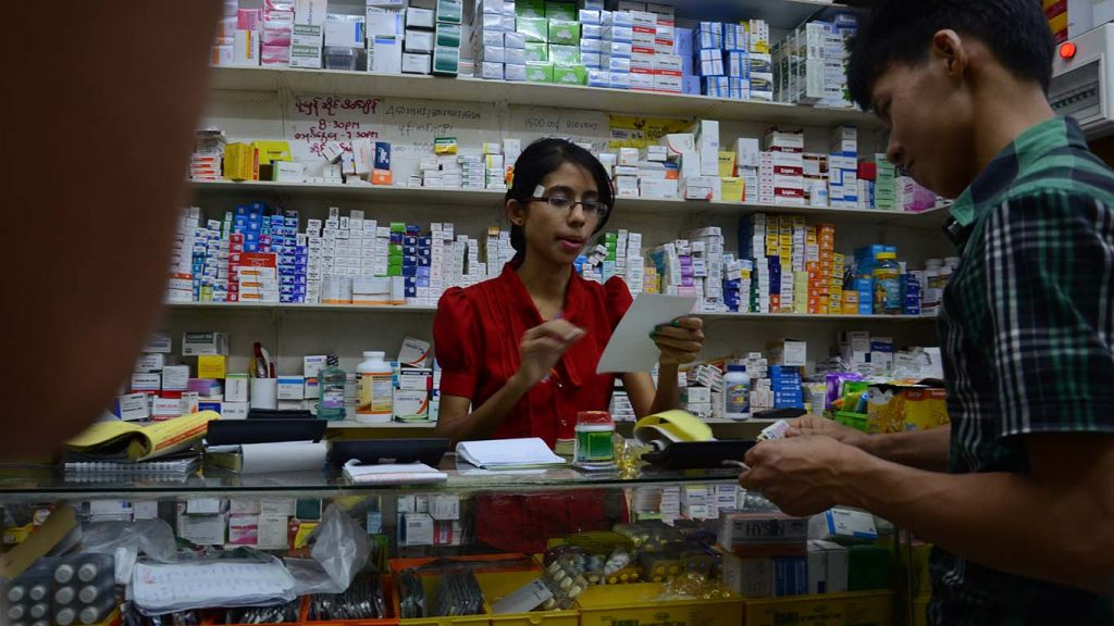 A customer buys medicine at a pharmacy. Photo: Phoe Khwar