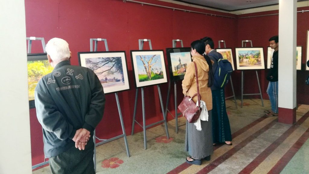 Painting onlookers observe the  pictures displayed at the gallery. Photo: Thiha Ko Ko (Mandalay)