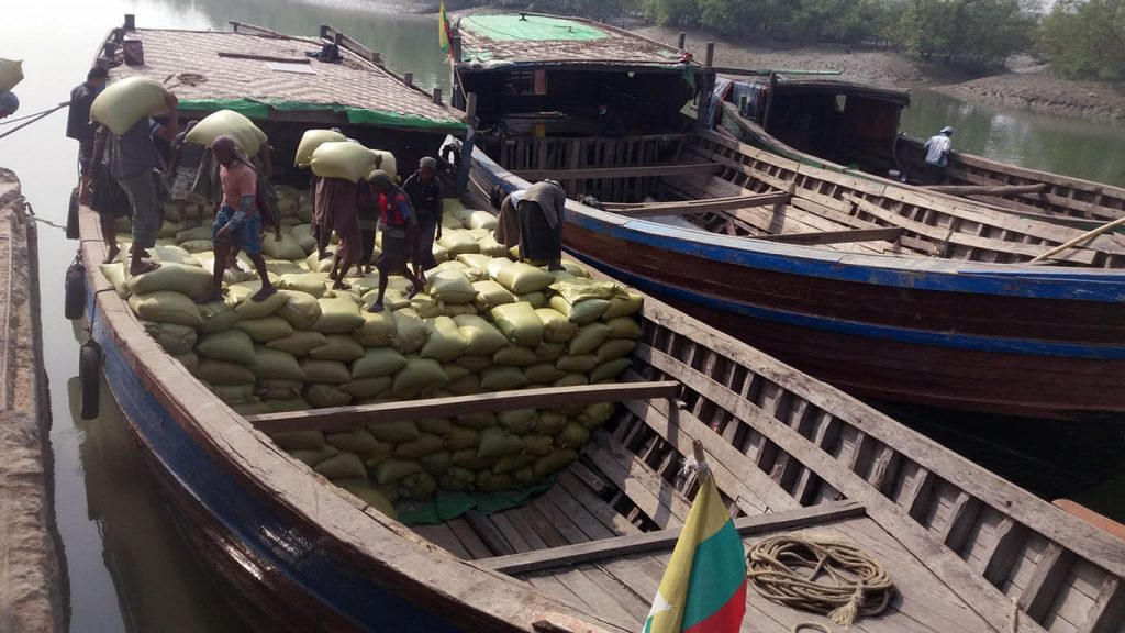 Workers unloading rice bags at the jetty in Maungtaw Trade Zone.Photo: Aung Min