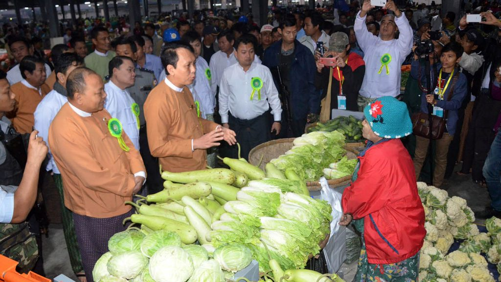 Yangon Region Chief Minister U Phyo Min Thein meets with vegetable sellers at Danyingone wholesale fruit, vegetable and flower market in Yangon. Photo: Zaw Gyi