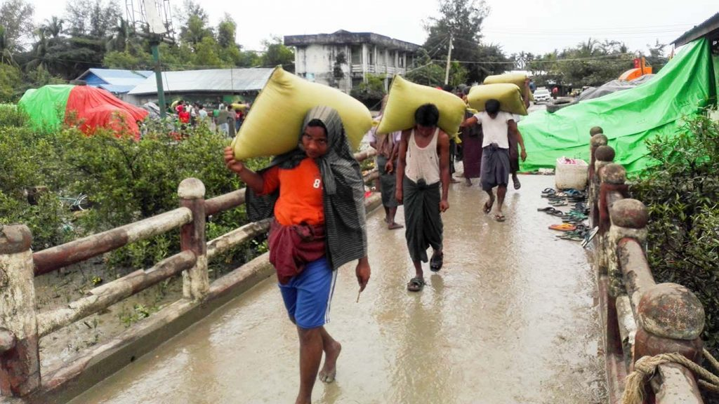 Workers carrying sacks of rice at the Maungtaw Border Trade Zone in Maungtaw.Photo: nay win tun