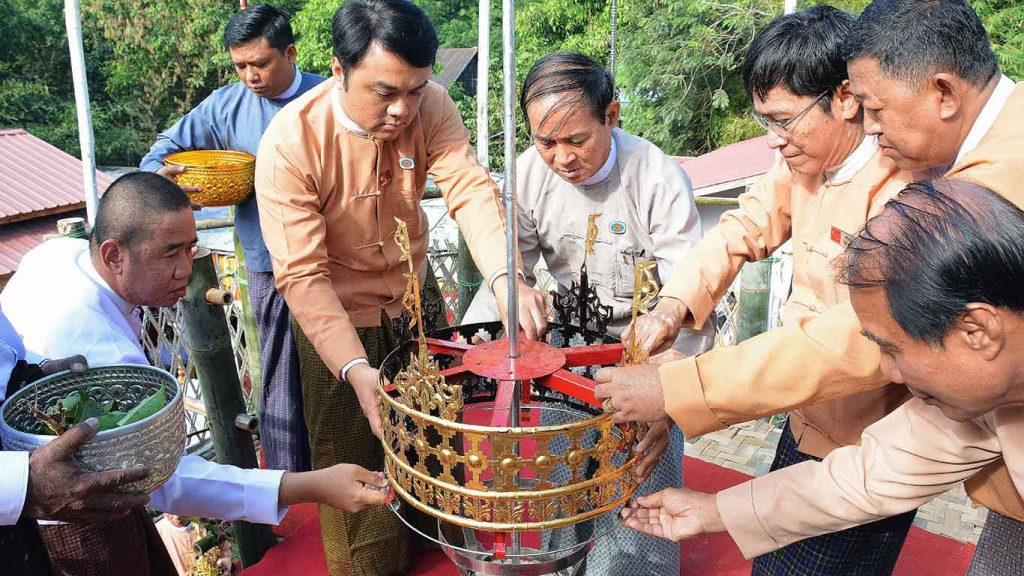 Pyithu Hluttaw Speaker U Win Myint and well-wishers fix the tiers of golden umbrella to Nan Oo Pagoda in Danubyu Township in Ayeyawady Region.Photo: MNA