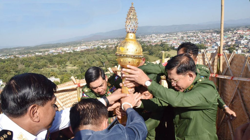 Senior General Min Aung Hlaing installs the diamond orb and pennant-shaped vane atop the Tachilek Shwedagon Pagoda in Tachilek.Photo: C-in-C Office